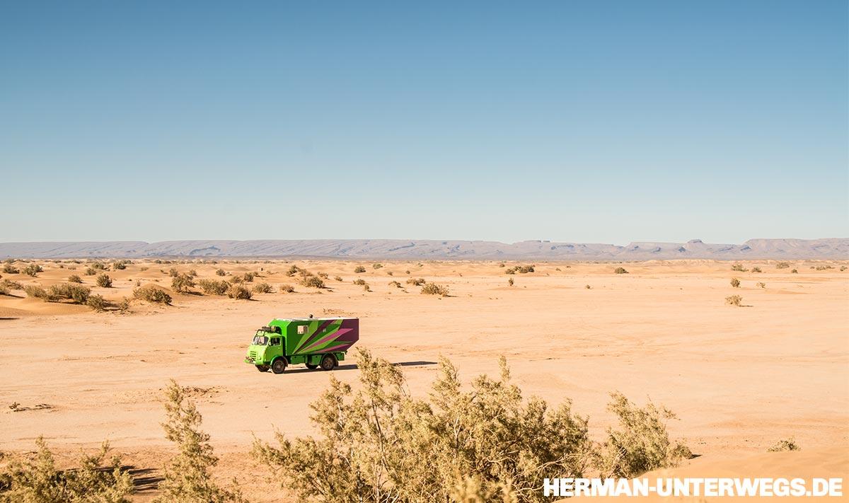 Unser grünes Wohnmobil in der Wüstenlandschaft vor Erg Chegaga