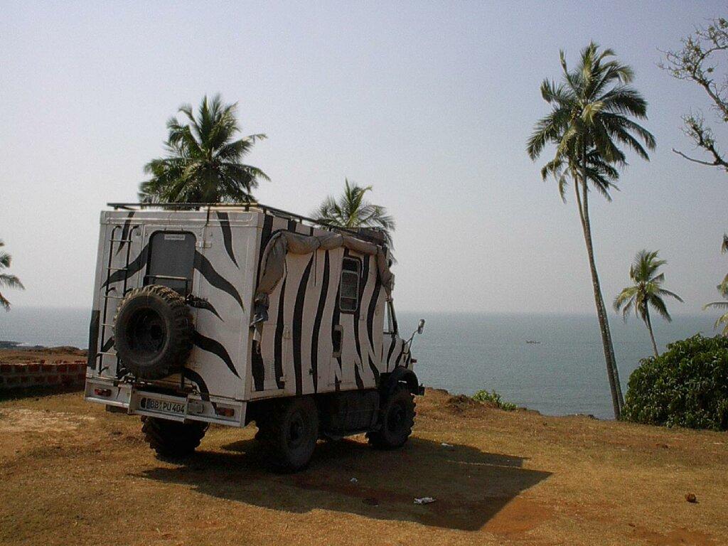 Unimog 404s im Zebradesign mit Stellplatz am Meer unter Palmen