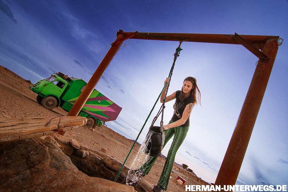 Sabine schöpft Wasser für das Wohnmobil am Brunnen, so bleiben die Marokko Reisekosten klein