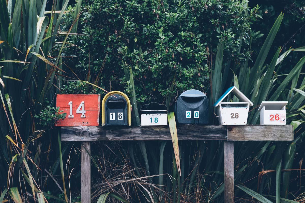 Verschiedene, kleine Briefkästen auf einer Holzleiste